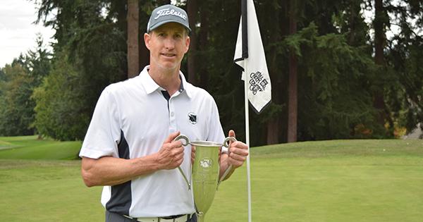Erik Hanson poses with the Men's Mid-Amateur perpetual trophy.